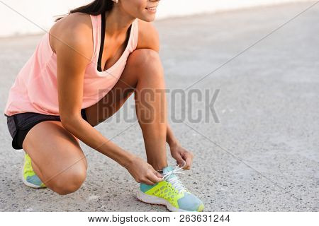 Cropped photo of beautiful woman 20s in tracksuit squatting and tying her sneaker laces on boardwalk during workout at seaside