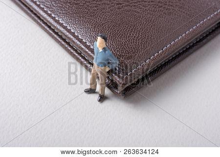 Tiny Figurine Of Man Miniature Model Beside A Wallet