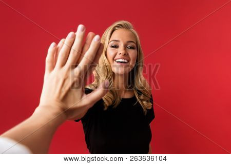 Image of young excited woman looking camera give a high five to someone's hand isolated over red background.