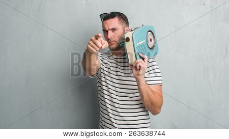 Young caucasian man over grey grunge wall listening music on vintage radio pointing with finger to the camera and to you, hand sign, positive and confident gesture from the front