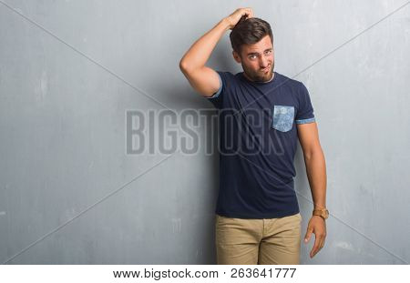 Handsome young man over grey grunge wall confuse and wonder about question. Uncertain with doubt, thinking with hand on head. Pensive concept.