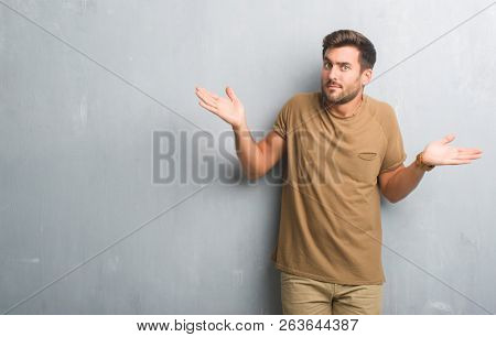 Handsome young man over grey grunge wall clueless and confused expression with arms and hands raised. Doubt concept.