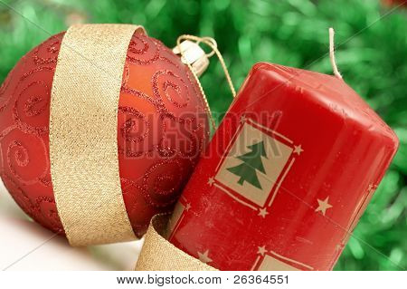 red candle and globe tied with a golden ribbon against green tinsel background