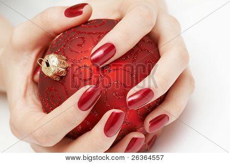 hands holding precious red Christmas globe