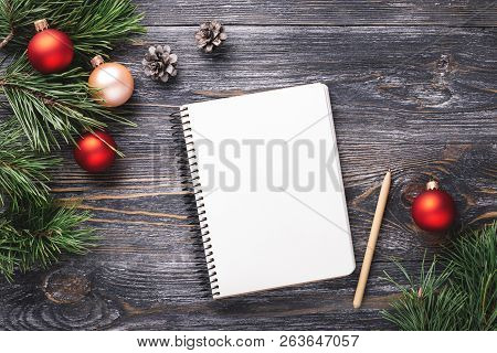 Mockup With White Paper Notebook And Christmas Decorations On Wooden Table. Top View.