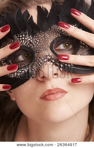 Young woman wearing black feathered carnival mask