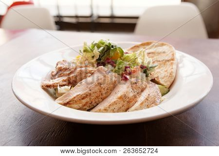 Grilled chicken breast and Greek pita with salad, food court food