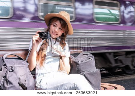 Travel Concept. Attractive Young Woman Hand Holding Camera And Travel Bag Sitting At The Train Stati