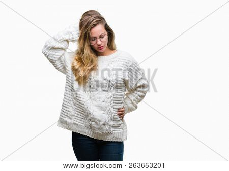 Young beautiful blonde woman wearing winter sweater and sunglasses over isolated background confuse and wonder about question. Uncertain with doubt, thinking with hand on head. Pensive concept.