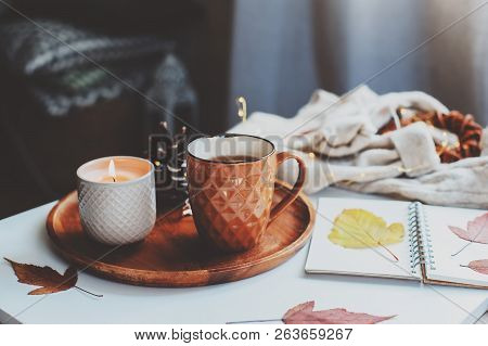 Cozy Autumn Or Winter Morning At Home. Still Life Details With Cup Of Tea, Candle, Sketch Book With