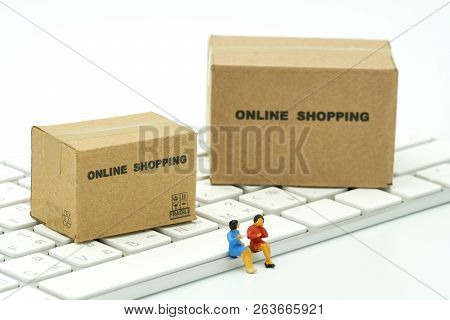 Miniature Two People Sitting On White Keyboard Online Shopping With A Shopping Cart And Shopping Bag