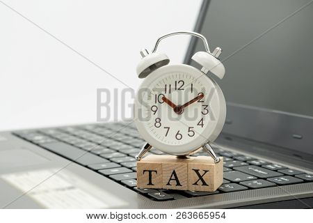 Tax Time Watches Put On The Wood Word Tax And White Keyboard Using As Background Business Concept An