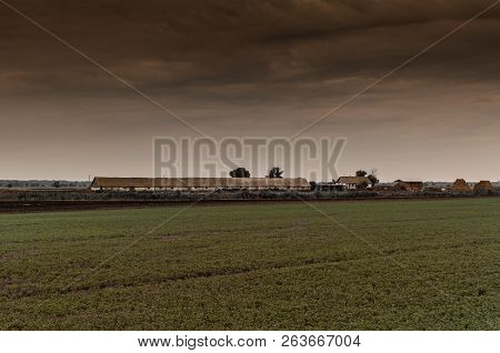 Gloomy Rural Landscape. Barn In The Field Against The Backdrop Of A Stormy Sky
