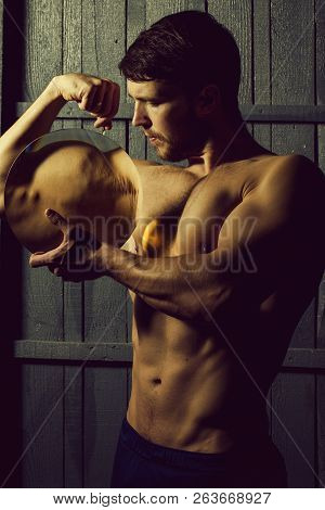 Handsome Man Is Holding Loupe And Showing His Muscles