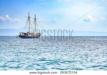 Sailboat On A Clam Sea With Blue Sky