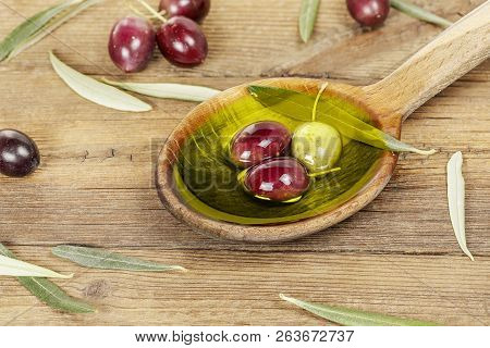 Wooden Ladle With Olive Oil And Olives On Weathered Table