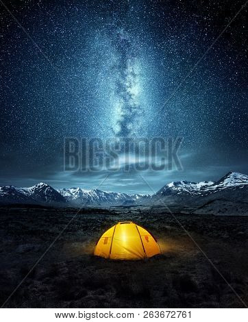 Camping In The Wilderness. A Pitched Tent Under The Glowing  Night Sky Stars Of The Milky Way With S