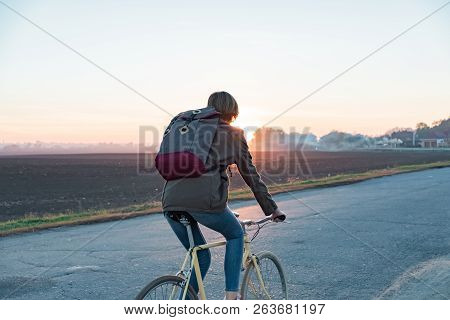 Female Commuter Riding A Bike Out Of Town To A Suburban Area. Young Woman Goes Home By Bike From Wor