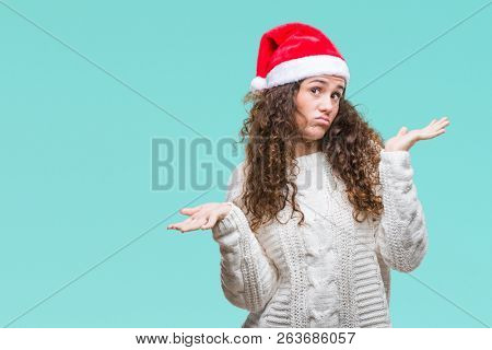 Young brunette girl wearing christmas hat over isolated background clueless and confused expression with arms and hands raised. Doubt concept.