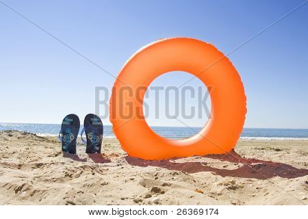 holiday background; orange ring buoy and blue slippers on the beach in summer