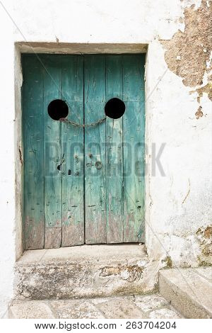 Specchia, Apulia, Italy - An Old Wooden Door Tightened With A Steel Track