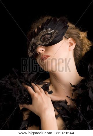 attractive blond woman wearing black carnival mask and feathers around her body, role play