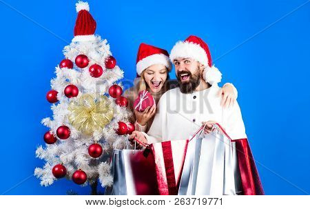 Happy Family Couple In Sweaters&santa Hats Holds Gifts Or Presents. Smiling Couple With Shopping Bag