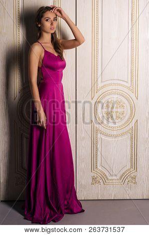 Fashion Portrait Of A Woman In A Beautiful Long Evening Dress, Near The Big White Doors. Luxurious I