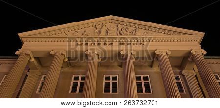 Facade And Pediment At Night Of The Danish Bank In Copenhagen With Big Columns In Ionic Order And A