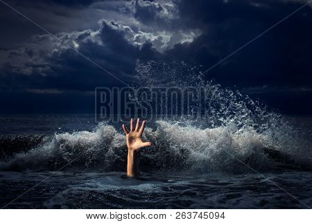 drowning man hand in storm sea water