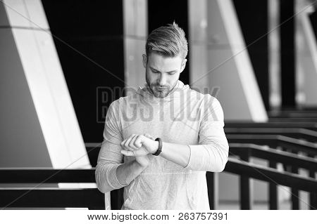 Man Athlete On Strict Face Checking Fitness Tracker, Urban Background. Athlete With Bristle With Fit