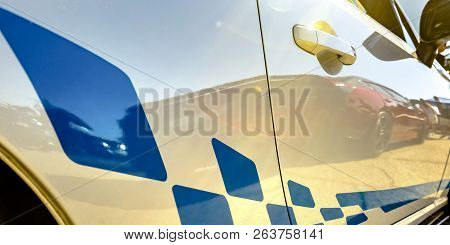 Blue Stripe Decal On A Reflective White Car
