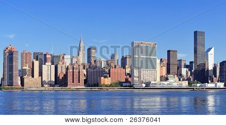 Manhattan midtown skyline panorama over East River with urban skyscrapers and blue sky in New York City