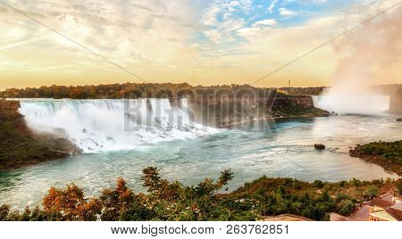 Panorama Of Golden Sunrise Over Niagara Falls Showing The Famous Waterfalls Of American Falls And Br