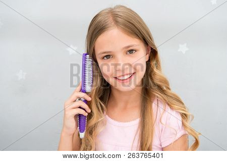 Girl long curly hair grey interior background. Child curly hairstyle hold hairbrush or comb. Apply oil before combing hair. Healthy hair. Conditioner or mask organic oil comb hair. Beauty salon tips. poster