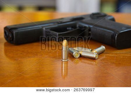 .38 Mm Handgun And Bullets Strewn On The Rustic Wooden Table Background. Gun With Ammunition And Iso