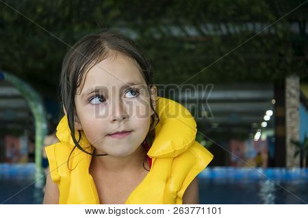 Close Up Of A Wet-haired Little Girl In Swim Vest With A Thoughtful Curious Look On Aquapark Backgro