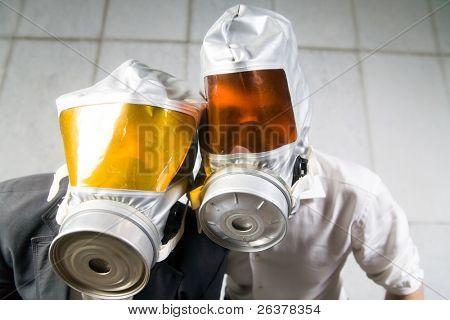 Two men wear gas masks