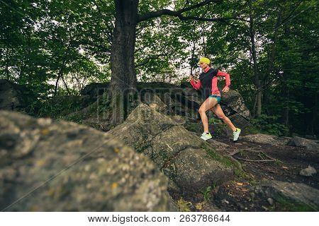 Trail Running Girl In Green Forest. Endurance Sport Training. Female Trail Runner Cross Country Runn