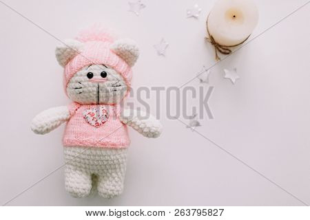 Handmade knitted toy cat on white background. Hello kitty. flat lay, top view poster