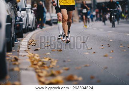 Marathon Running Race, People Feet On Autumn Road. Runners Run Urban Marathon In The The City. Group