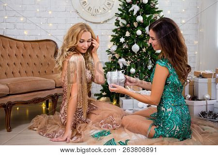 Christmas Tradition Concept - Two Beautiful Women In Dresses With Gift Boxes In Living Room With Dec