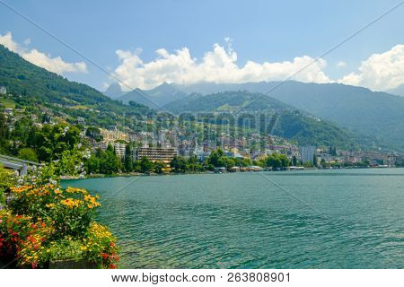View to Montreux city from Geneva lake embankment at sunny summer day, flowers at foreground.