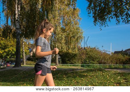 Happy Teen Girl Runs On Green Grass. The Girl Loves To Run And Enjoys Jogging. The Teenager Is Happy