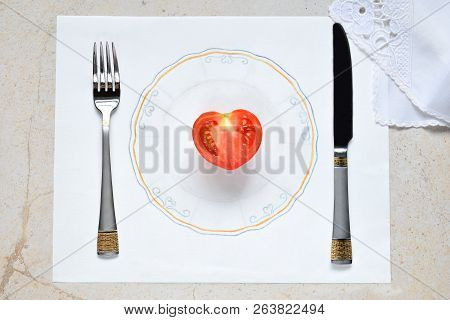 Half A Tomato In The Form Of A Heart On A Painted Plate. Concept Of Vegetarian Food. Restrictions On