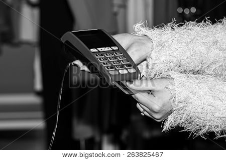 Female Hand Puts Bankcard Into Reader On Defocused Background