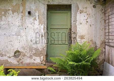Green Wooden Door, Dirty Grunge Stucco Wall Background.
