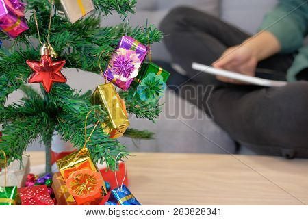 Man Sitting On Sofa Using Tablet At Home. Woman Holding Touchpad During Xmas. Christmas Holiday New