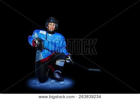 Young Hockey Player Spotlighted On Dark Background