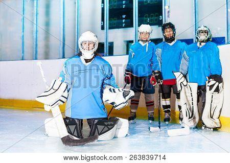 Girl Goaltender In Butterfly Position On Ice Rink